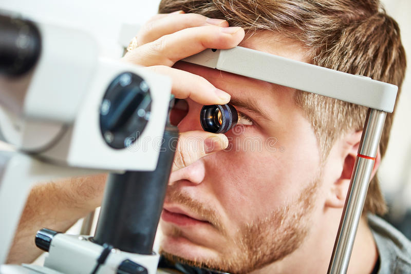Ophthalmology eyesight examination. Ophthalmology concept. Male patient under eye vision examination in eyesight ophthalmological correction clinic royalty free stock image