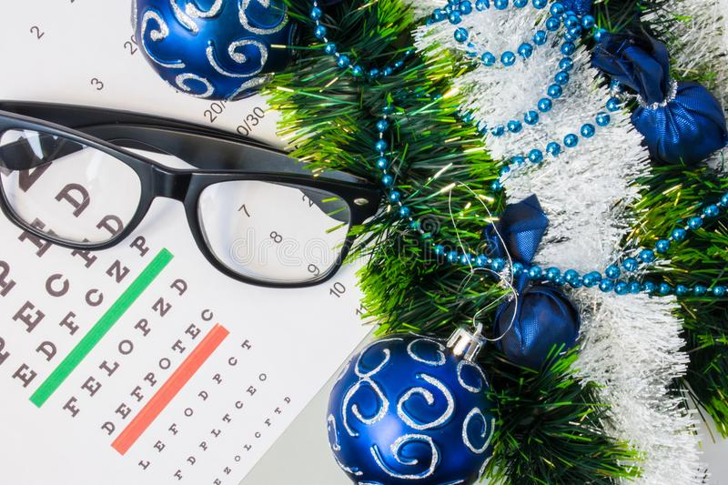 Ophthalmology or optometry Christmas and New Year with decorations. Eyeglasses and table for measure visual acuity lying near arti stock images