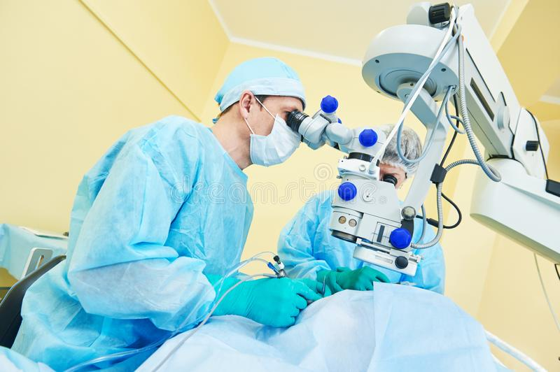Ophthalmology. surgeon doctors in operation room. Surgeon team in uniform in front of eye vision surgery operation room at medical ophthalmology clinic stock photos