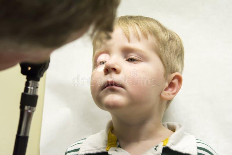 Ophthalmoscope som används på ung pojke royaltyfria foton