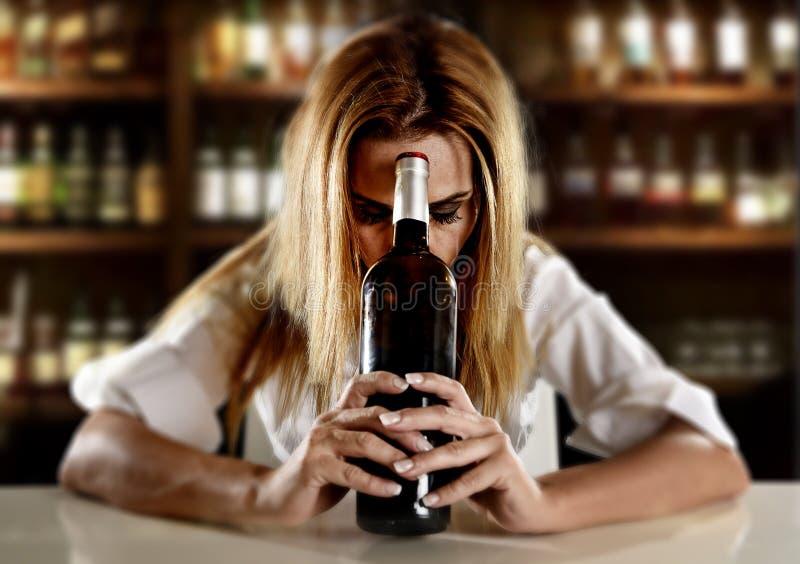 Opiła alkoholiczna blond kobieta samotnie w zmizerowany przygnębionym z czerwone wino butelką w barze obraz stock