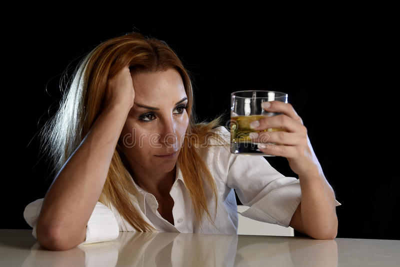 Opiła alkoholiczna kobieta marnotrawiąca i deprymująca trzymający patrzeć rozważny scotch whisky szkło zdjęcie stock
