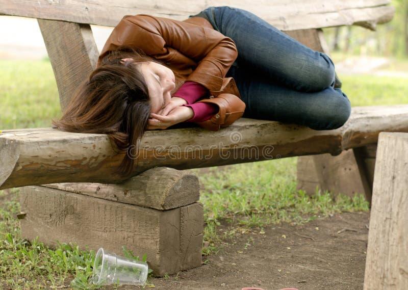 Opiła kobieta śpi mnie daleko na drewnianej ławce obrazy stock