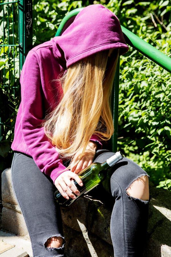 Opiła młoda kobieta z butelką alkohol zdjęcie stock