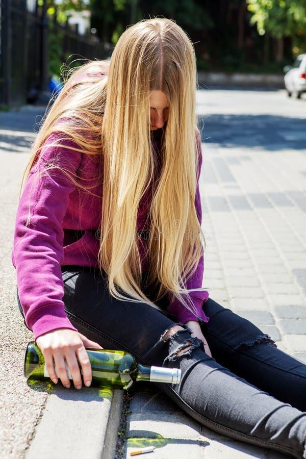 Opiła młoda kobieta z butelką alkohol fotografia stock