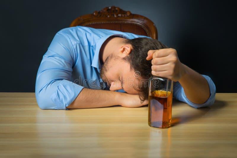 Opiły mężczyzna pije alkohol przy stołem fotografia stock