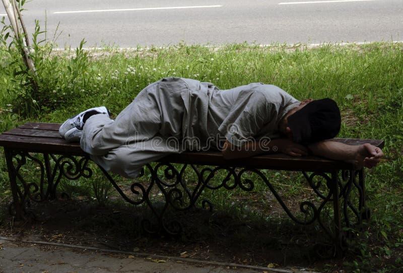 Opiły mężczyzna spadał uśpiony na ławce zdjęcie royalty free