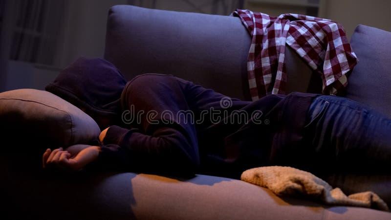 Opiły nastolatek w hoodie cierpienia kac objawach po przyjęcia, kłama w łóżku zdjęcie stock