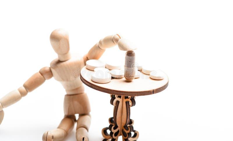 Opieka zdrowotna i leczenie Pigułki na malutkim drewnianym stole Lekarstwo reżim Ludzka drewniana atrapa blisko zgłasza z obrazy stock