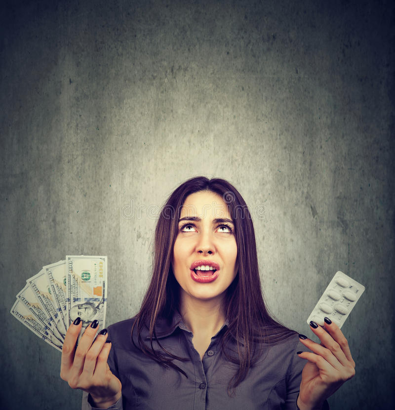 Opieka zdrowotna koszty Sfrustowana kobieta z pigułkami i dolarowymi banknotami obrazy royalty free