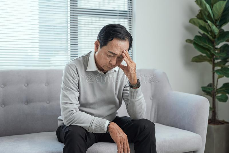 Opieka zdrowotna, stres, staro?? i ludzie poj??, - starszego m??czyzny cierpienie od migreny w domu obraz stock