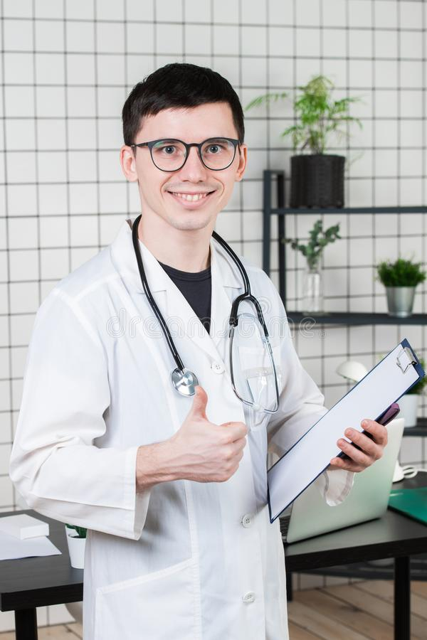 Opieka zdrowotna, zawód i medycyny pojęcie, - uśmiechniętej samiec doktorskie pokazuje aprobaty nad medycznym biurowym tłem obraz royalty free