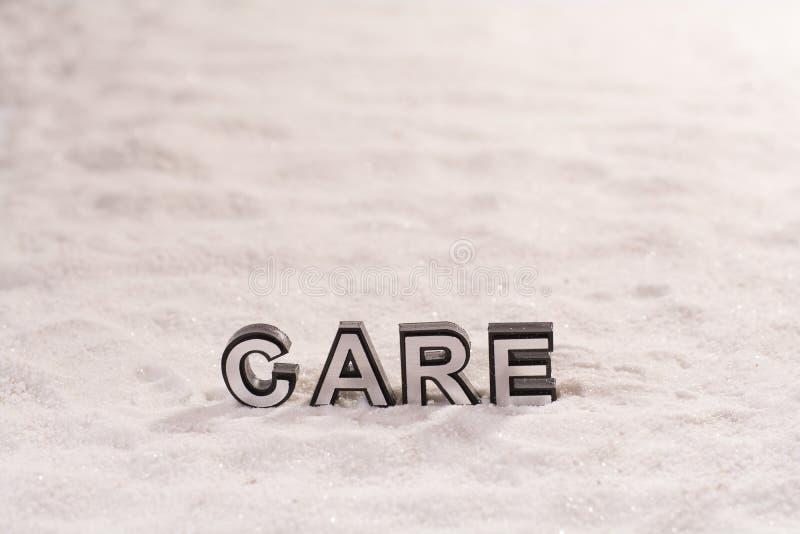 Opieki słowo na białym piasku zdjęcie royalty free