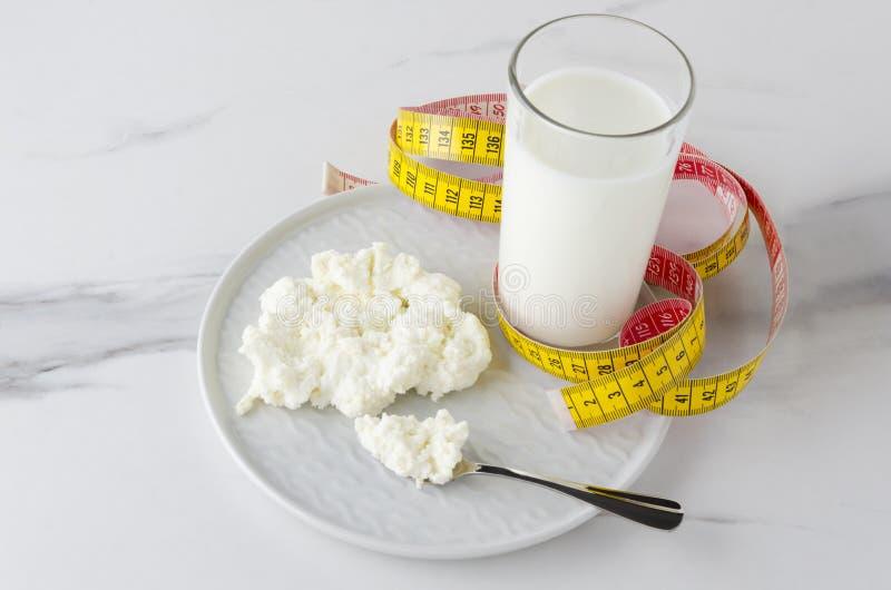 Opieki zdrowotnej i łasowania zdrowie jedzenie Ogląda twój talię i postać Miara taśmy, mleko, chałupa ser zdjęcia stock