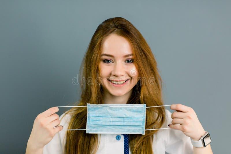 Opieki zdrowotnej i medycyny pojęcie - żeńskiego uśmiechniętego potomstwa doktorskiego mienia medyczna maska, odosobniona na szar obraz royalty free