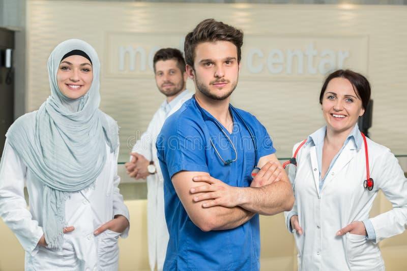Opieki zdrowotnej i medycyny pojęcie - atrakcyjna samiec lekarka przed medyczną grupą w szpitalu pokazuje aprobaty obraz stock