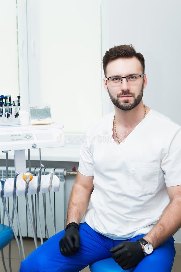 Opieki zdrowotnej, zawodu, stomatology i medycyny pojęcie, - uśmiechnięty męski młody dentysta nad medycznym biurowym tłem zdjęcie stock
