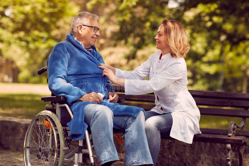 Opiekun pielęgniarka pomaga niepełnosprawnego starszego pacjenta w wózku inwalidzkim fotografia stock