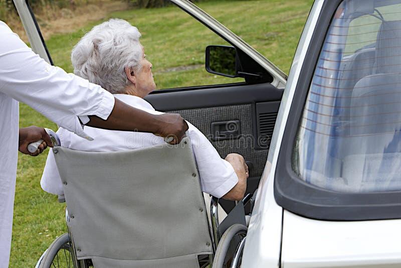 Opiekun pomaga niepełnosprawnej starszej damy dostawać inside jej samochód obraz stock