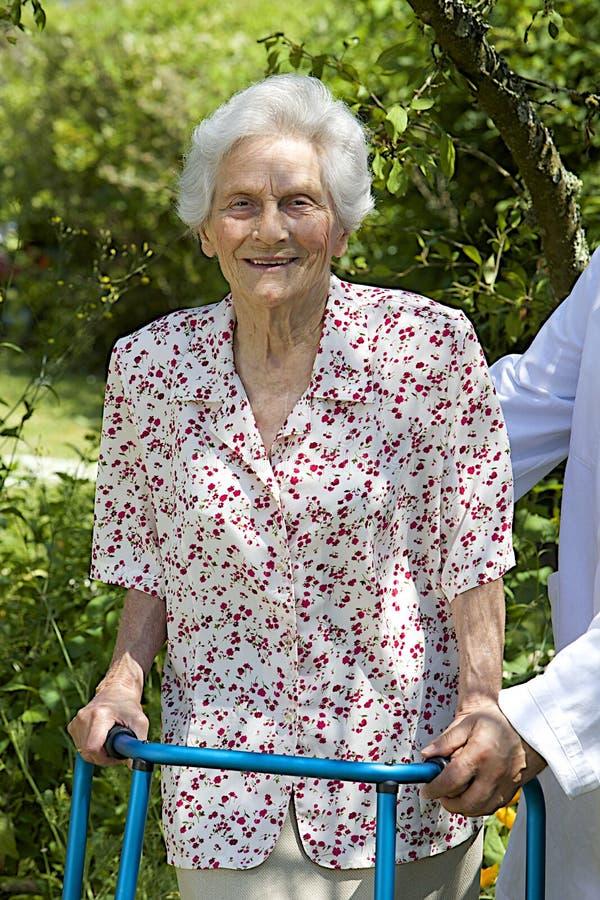 Opiekun pomaga starszego pacjenta z jej piechurem zdjęcia stock