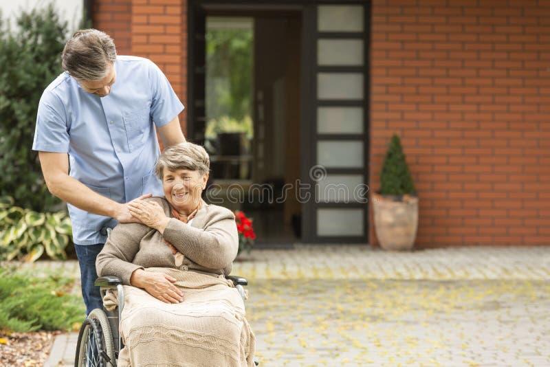 Opiekun pomaga u?miechaj?cy si? niepe?nosprawnej starszej kobiety w w?zku inwalidzkim przed domem zdjęcie stock