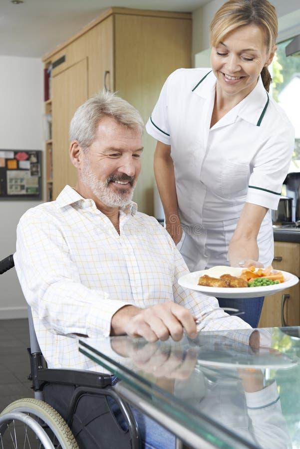 Opiekun porci posiłek Obsługiwać W wózku inwalidzkim W Domu fotografia stock