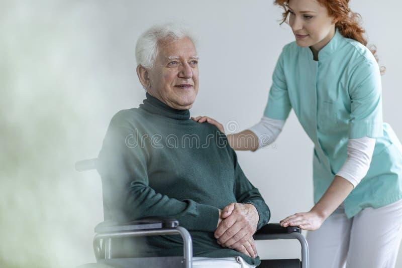 Opiekun wspiera szczęśliwego niepełnosprawnego starszego mężczyzna w wózku inwalidzkim ja zdjęcia stock