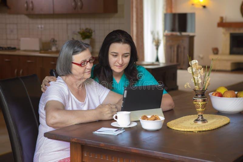 Opiekun z starszą kobietą używa cyfrową pastylkę w domu zdjęcie stock