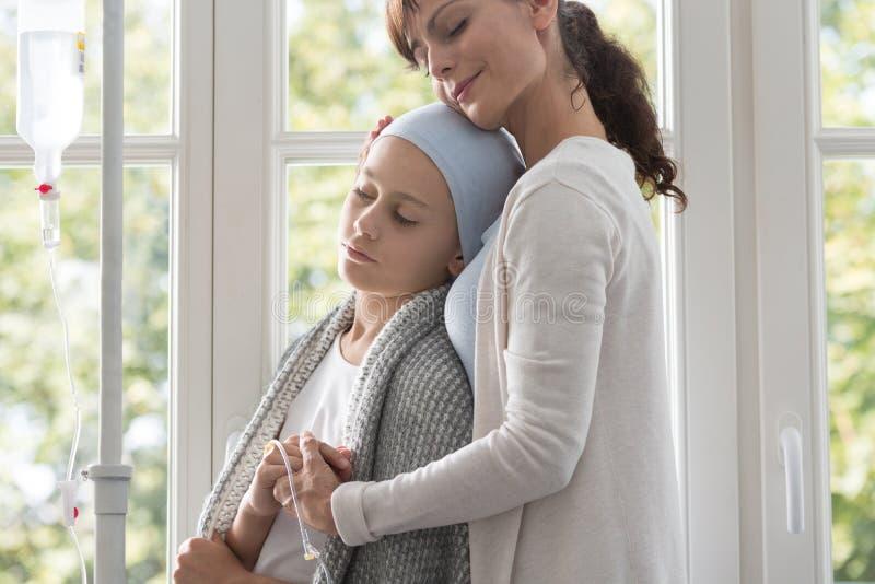 Opiekunu przytulenia chory dziecko z nowotworem jest ubranym chustkę na głowę obraz royalty free