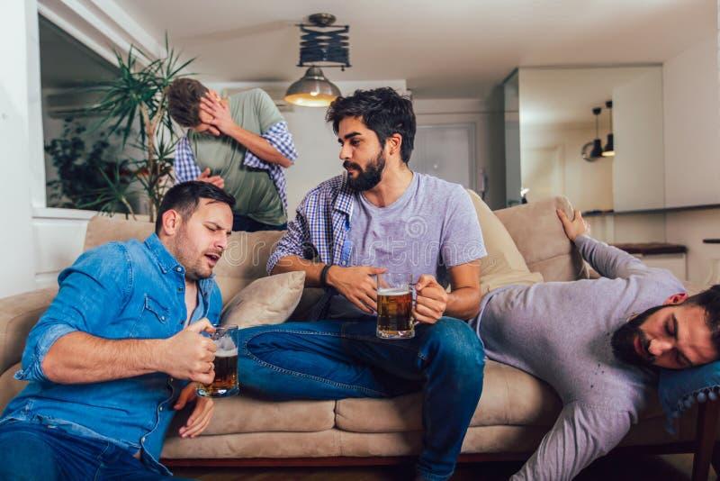 Opili faceci ?pi? po nocy wydarze? na kanapie w r??nej pozie w ?ywym pokoju i pod?odze obraz royalty free