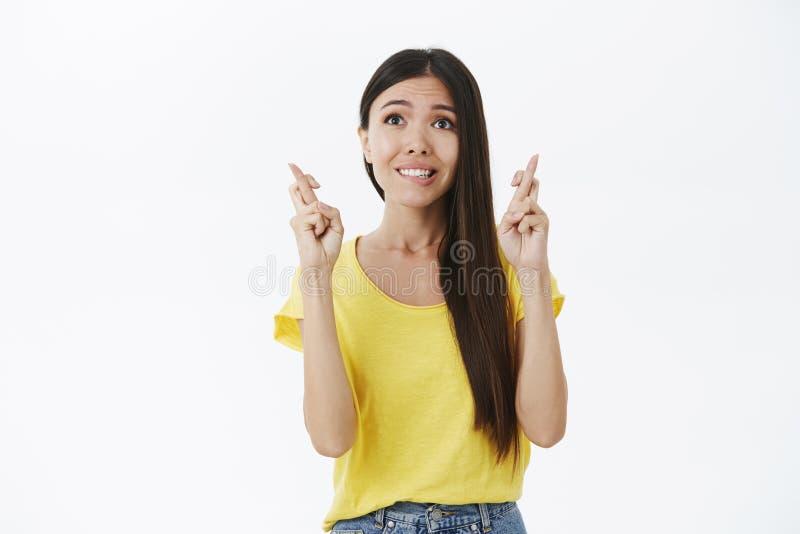 Opimistic e mulher magro encantador esperançosa com o bordo de mordedura longo do cabelo escuro e os dedos de cruzamento fiéis de imagens de stock