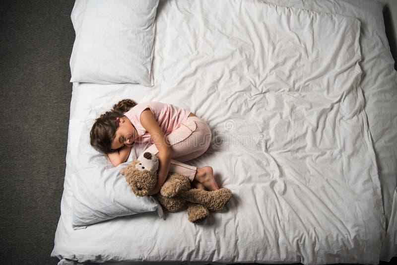 opinião aérea a criança adorável que abraça o urso de peluche ao dormir na cama imagem de stock royalty free