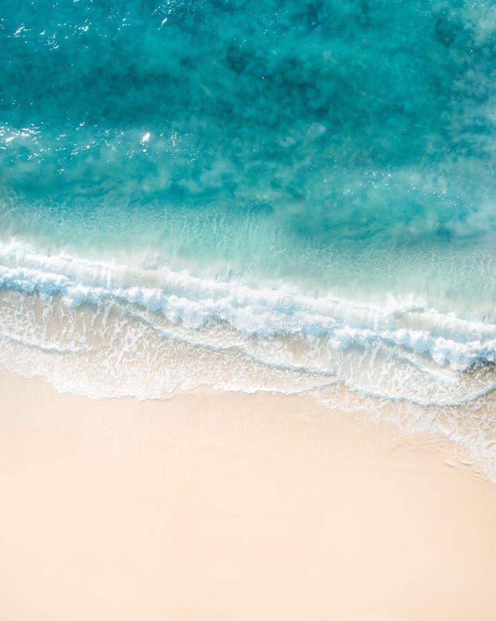 Opinião aérea da praia Vista superior agradável do oceano azul, da onda deixando de funcionar e da areia branca foto de stock royalty free