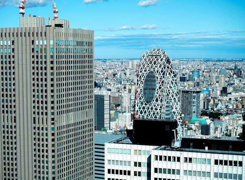 A opinião aérea da skyline moderna panorâmico da cidade das construções na área financeira no Tóquio e o céu azul vívido expõem a imagem de stock