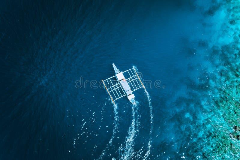 Opinião aérea do zangão do barco filipino tradicional branco que flutua sobre a superfície clara da água azul Nido do EL, Palawan fotografia de stock