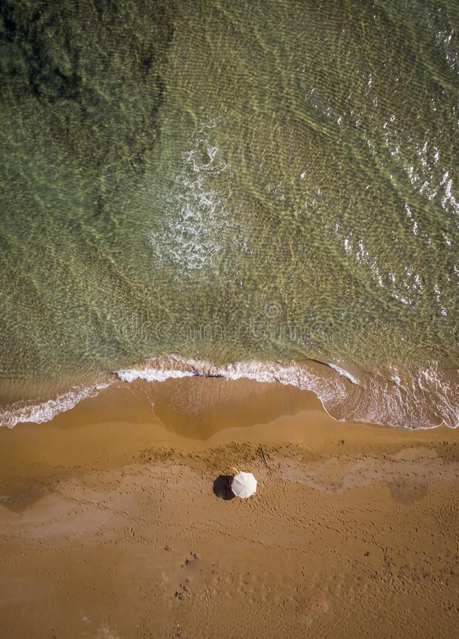Opinião aérea do zangão de uma praia isolado e de um guarda-chuva, águas claros Corfu Greece imagem de stock