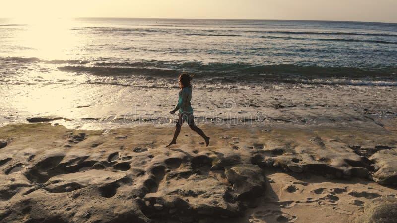 Opinião aérea do zangão a jovem mulher saudável no vestido que corre na praia tropical perto do oceano durante o por do sol bonit fotos de stock