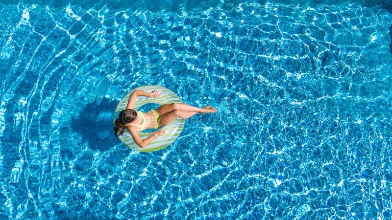 A opinião aérea a menina na piscina de cima de, na nadada da criança na filhós inflável do anel e tem o divertimento na água imagem de stock