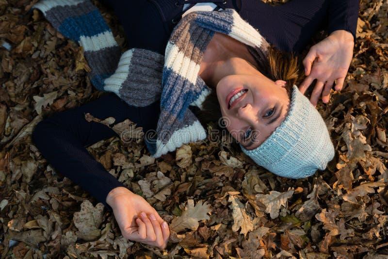 Opinião aérea a mulher feliz que encontra-se nas folhas secas imagens de stock