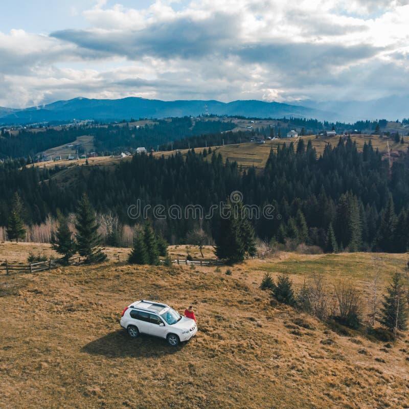 Opinião aérea o homem no revestimento vermelho perto do carro branco do suv no monte com Mountain View bonito fotos de stock