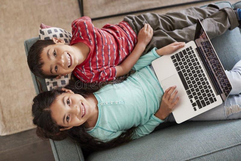 Opinião aérea o irmão And Sister Sitting em Sofa At Home Having Fun que joga no portátil junto fotografia de stock royalty free