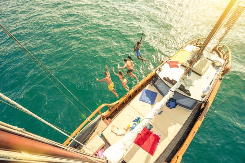Opinião aérea os amigos novos que saltam do barco de navigação no mar foto de stock