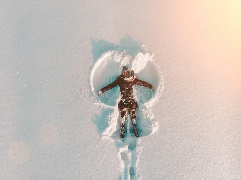 Opinião aérea superior a menina de sorriso feliz nova que faz pela figura do anjo da neve dos braços e que encontra-se na neve, a fotos de stock