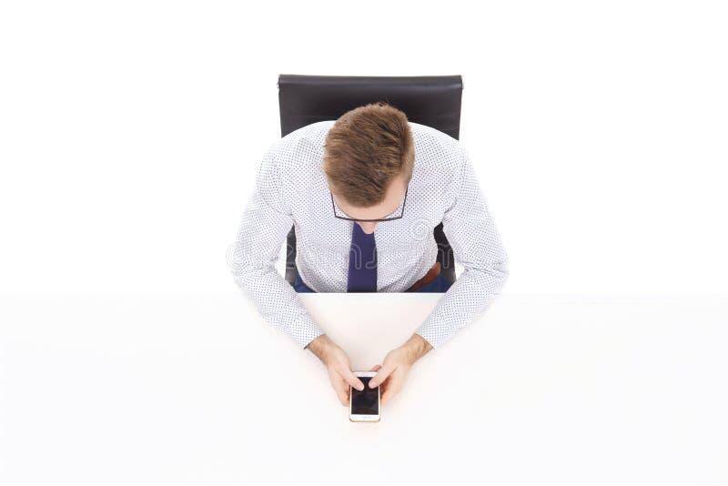 Opinião aérea um homem de negócios considerável com o smartphone em offic fotografia de stock royalty free