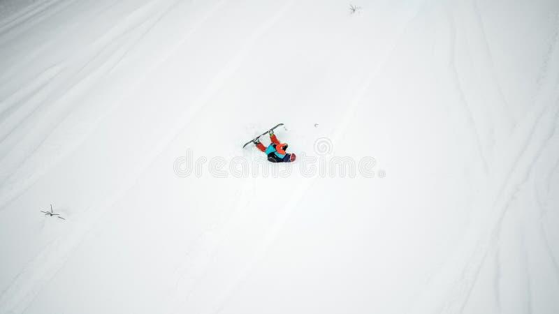 Opinião aérea um snowboarder que caísse durante a descida na neve foto de stock