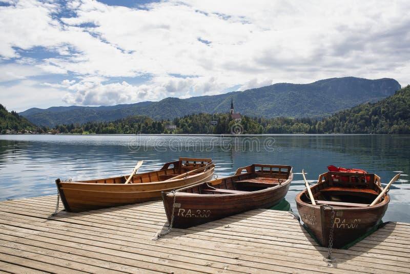 Opini?o agrad?vel da vista da igreja da suposi??o no lago sangrado do cais com barcos A maioria lago e de ilha eslovenos famosos  foto de stock