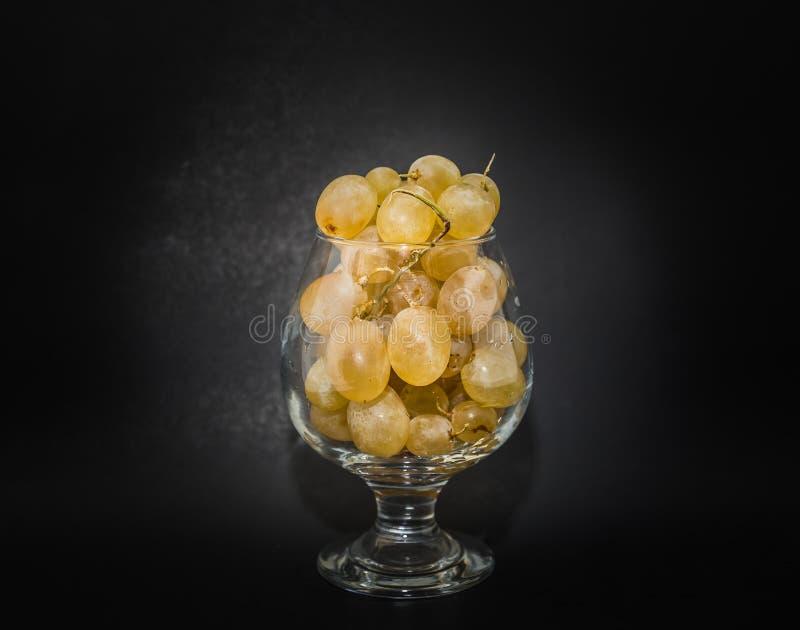 opinião agradável do close up bagas suculentas da uva de muscat no vidro de vinho claro fotos de stock
