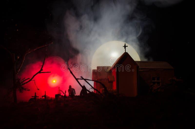 Opinião assustador os zombis na árvore inoperante do cemitério, na lua, na igreja e no céu nebuloso assustador com névoa, conceit foto de stock