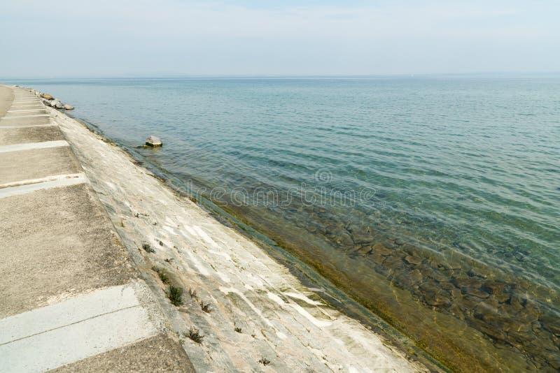 Opinião bonita da natureza da costa do lago com terraplenagem concreta e a parede que conduzem na água fotos de stock