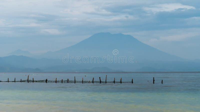 Opinião bonita da noite a St Agung Vulcano em Bali da ilha de Nusa Penida, rede na parte dianteira algumas nuvens no fundo fotos de stock royalty free